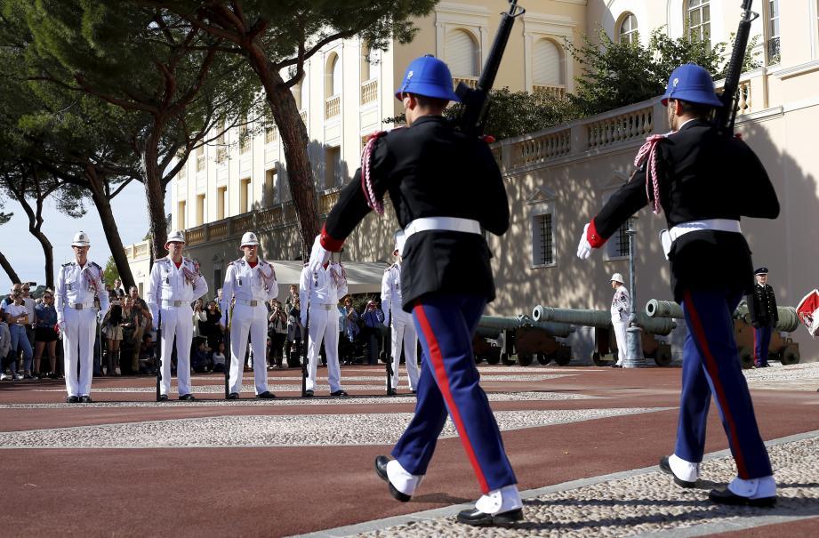 La relève avec changement de tenue de saison de la garde du palais princier à Monaco: la garde descendante en tenue blanche d'été, la garde montante en tenue noire-bleue marine d'hiver.