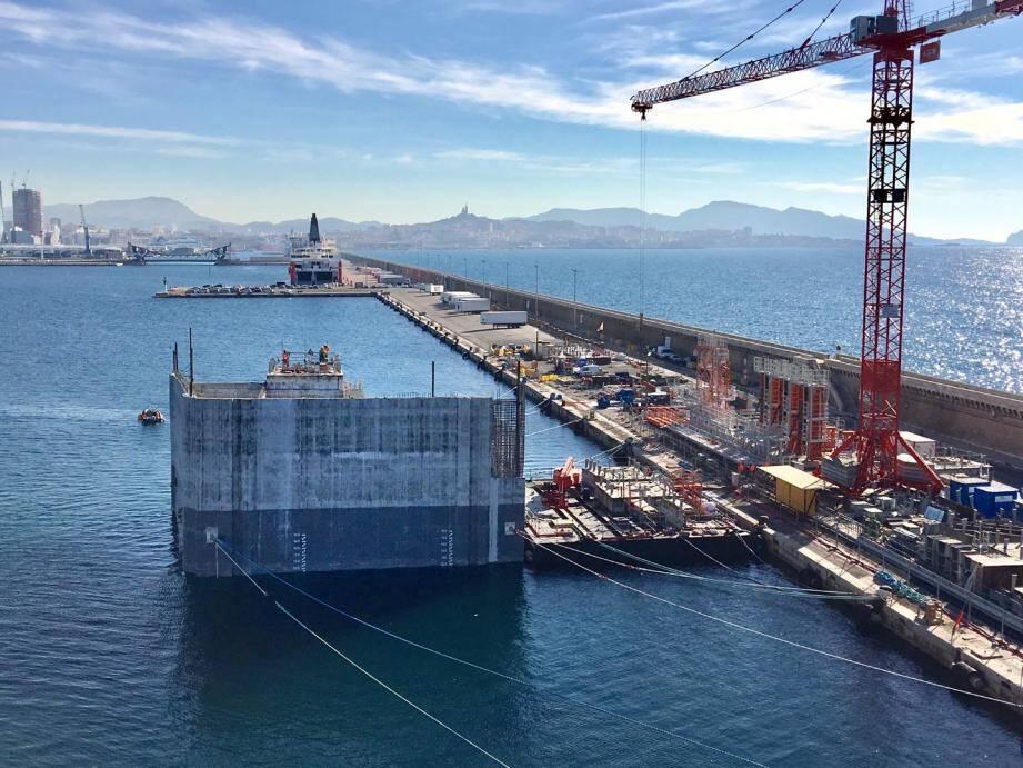 Non loin des navires flotte un colosse de béton de plus de 9000 tonnes, qui nécessite l'usage de grues exceptionnelles : 70 mètres de haut et une capacité de levage de 6.6 tonnes (contre 40 mètres et 3 tonnes habituellement).