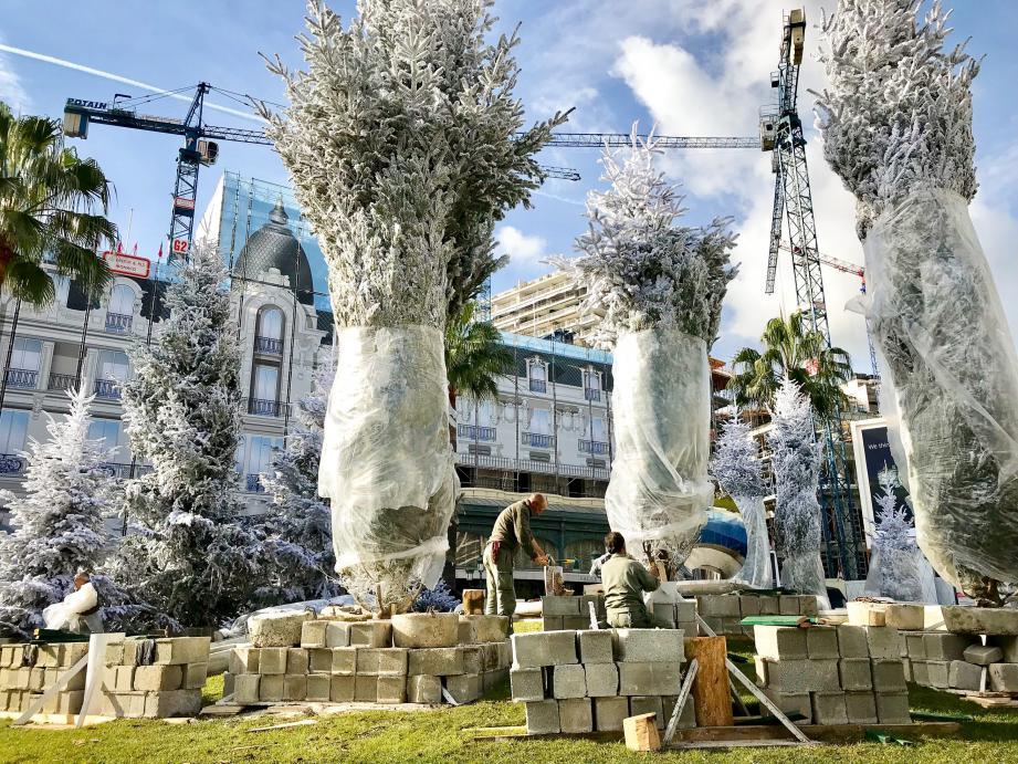À gauche, à la place de la fontaine, une boule à neiges géante sera installée pour marquer le thème des jeux. À droite, les sapins, floqués en blanc, sont arrivés place du Casino.
