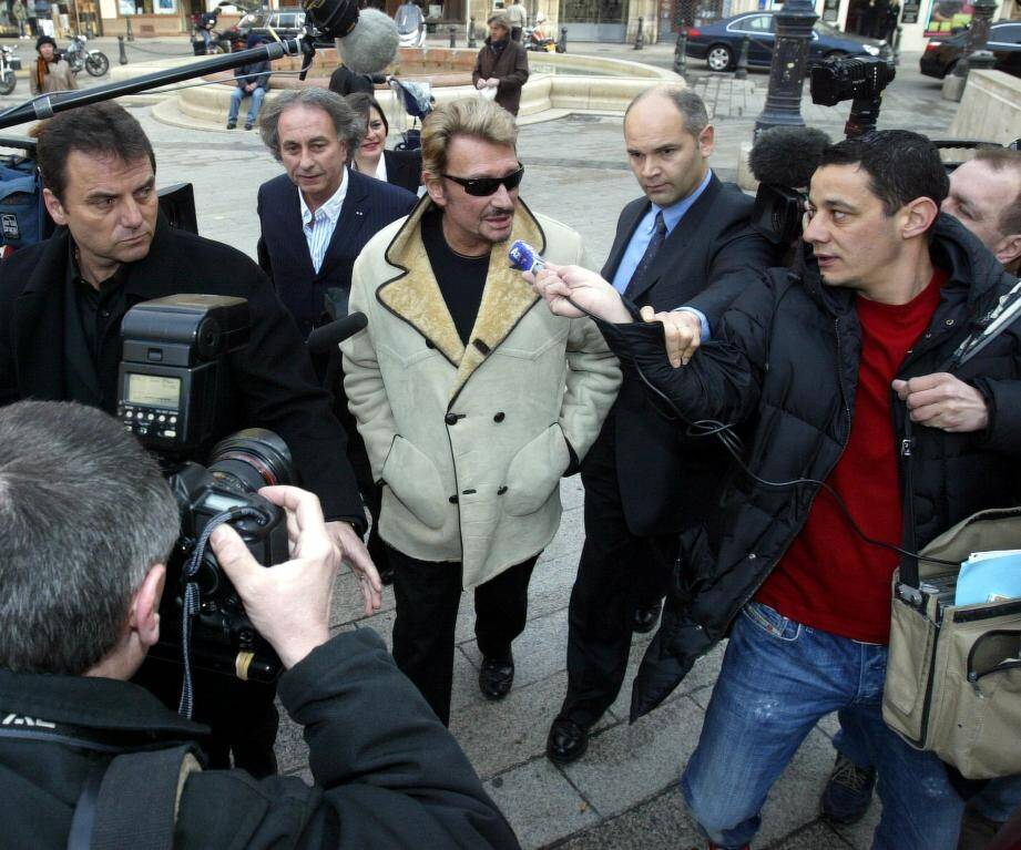 Francis Moya, à gauche, accompagnant Johnny sur la place du palais de Justice de Nice avec l'avocat du chanteur en arrière-plan, Me Portejoie, et Jimmy son garde du corps parisien, à droite, en 2004.