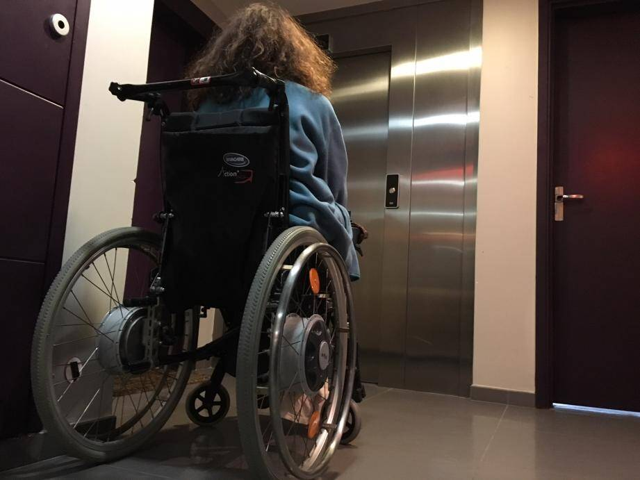 Sylvia dans son fauteuil roulant, bloquée au cinquième étage, face à l'ascenseur désespérément à l'arrêt.