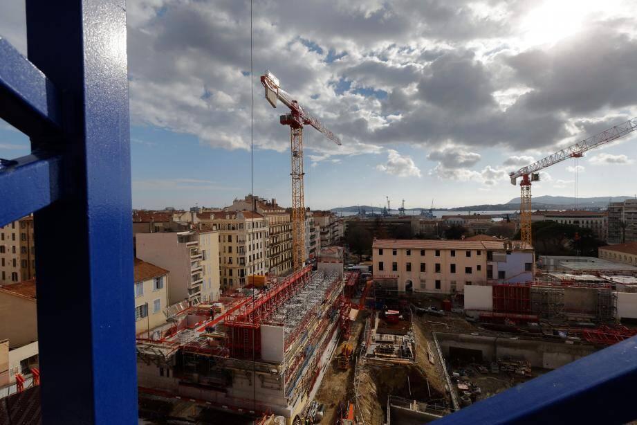 Les opérations de terrassement et de fondation achevées, le bâti peut commencer. Ici, le futur Palais de la connaissance et de l'industrie sort de terre (à gauche), tandis que les fondations de la résidence touchent à leur fin (à droite).