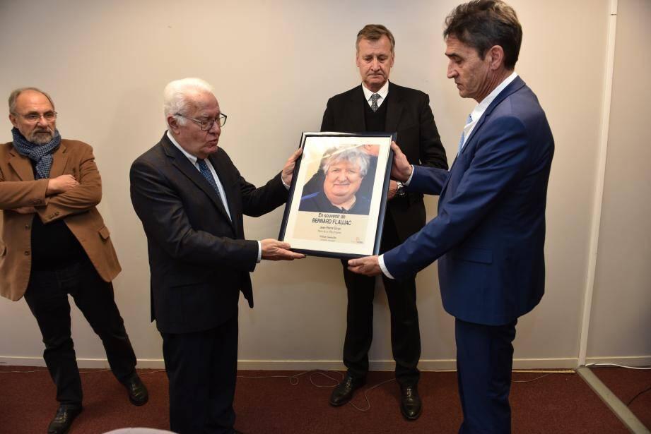 Le portrait de Bernard Flaujac tenu par le maire et le proviseur du lycée.