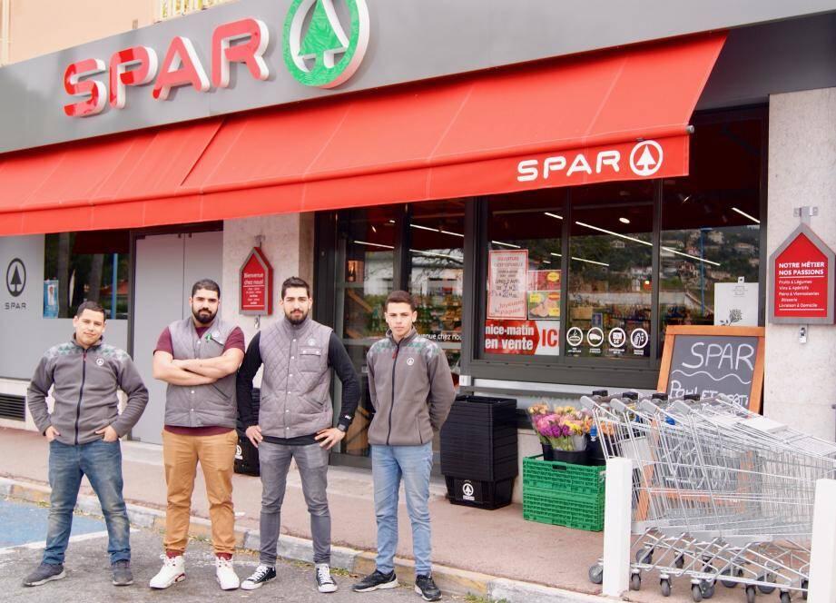 Les deux co-gérants, au centre, entourés de deux apprentis devant la devanture rénovée du magasin.