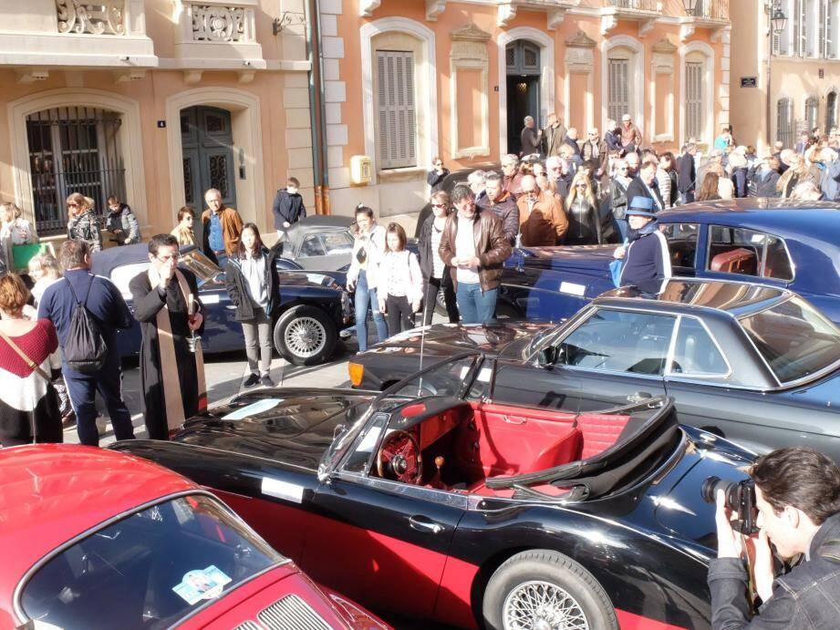 Le père Jean-Paul bénit les voitures avant le début de la « Bella Strada », au milieu d'une foule d'admirateurs de ces belles voitures.
