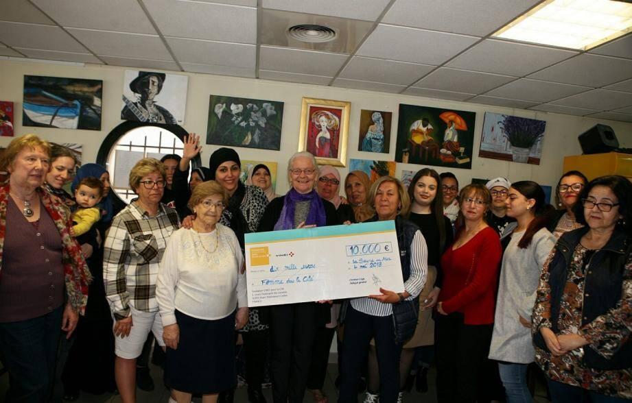 Dans le restaurant associatif Le Petit Prince, les membres de Femme dans la cité présentent le chèque de la fondation Vinci.