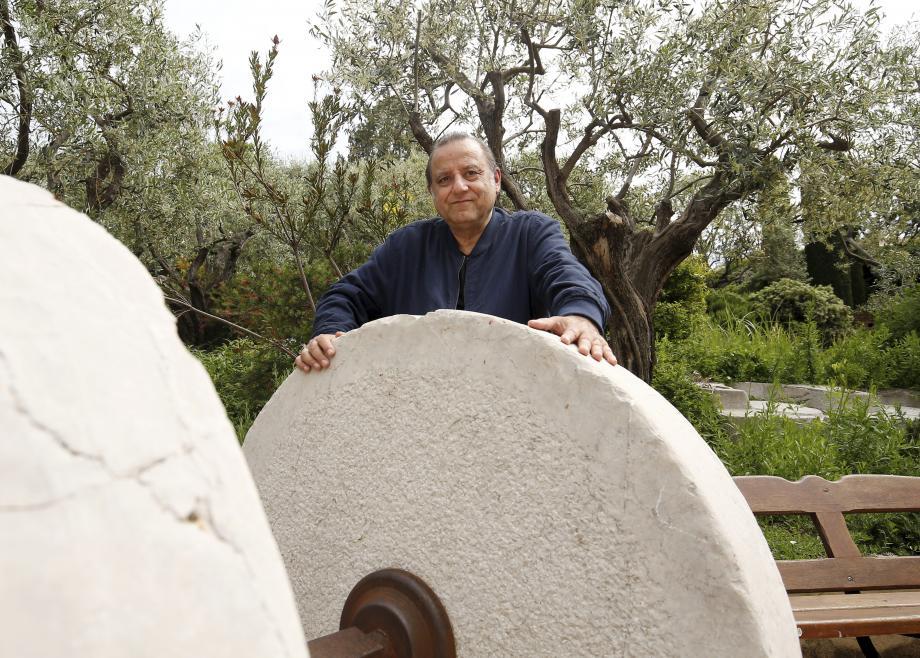 Claude Vaccarezza et les vestiges d'une meule d'un ancien moulin monégasque exposée place Saint Nicolas.