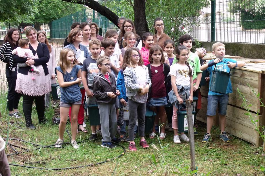 Élèves, parents et enseignants aux côtés des composteurs installés dans l'école.