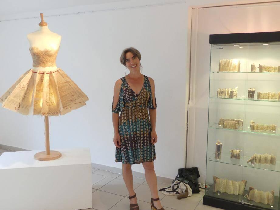 Aïdée Bernard devant sa robe créée en papier de correspondance.