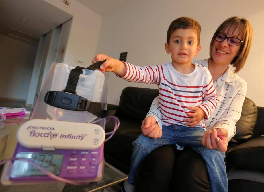 Sur les genoux de sa maman, Flavio tient la machine qui sert à l'alimenter.