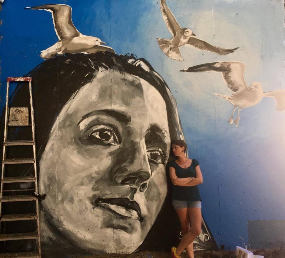 Nicola Schmid pose avec Amie. Elle s'est inspirée d'une photo pour réaliser la fresque.