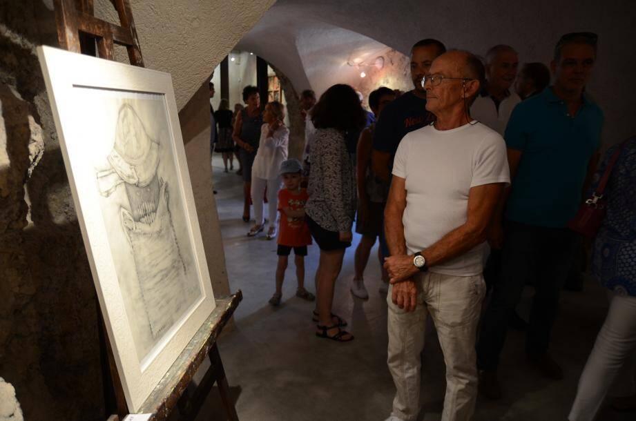Les visiteurs observent les tableaux exposés dans le château.
