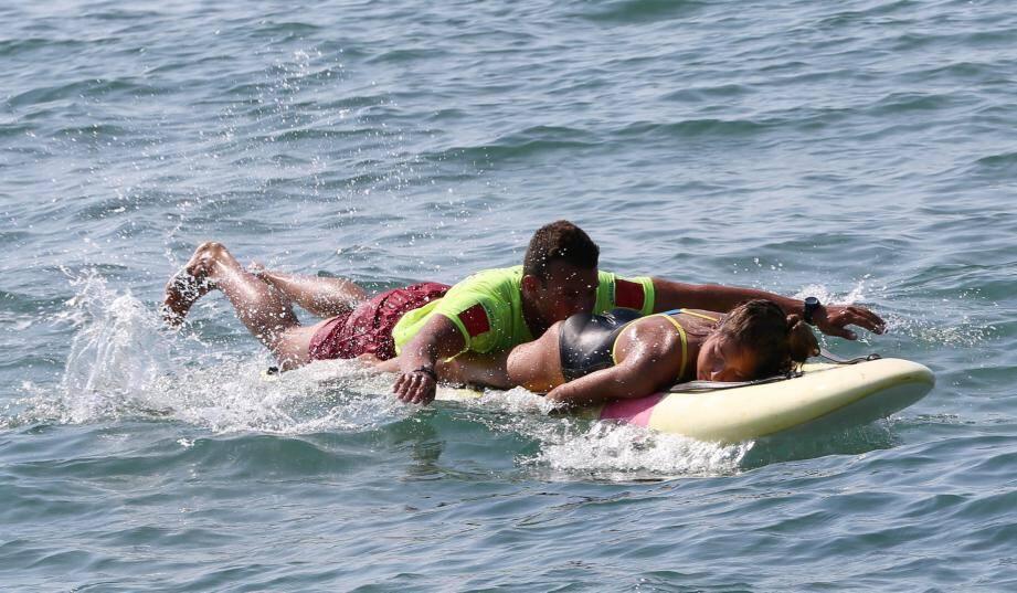 La victime est hissée sur la planche en la basculant, et ramenée sur le rivage où commence une intervention de premier secours, en attendant l'ambulance.