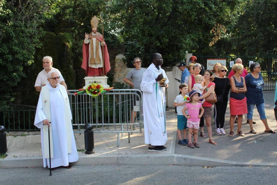 Devant la statue de saint Éloi, le père Sagna attendant les attelages afin de les bénir.