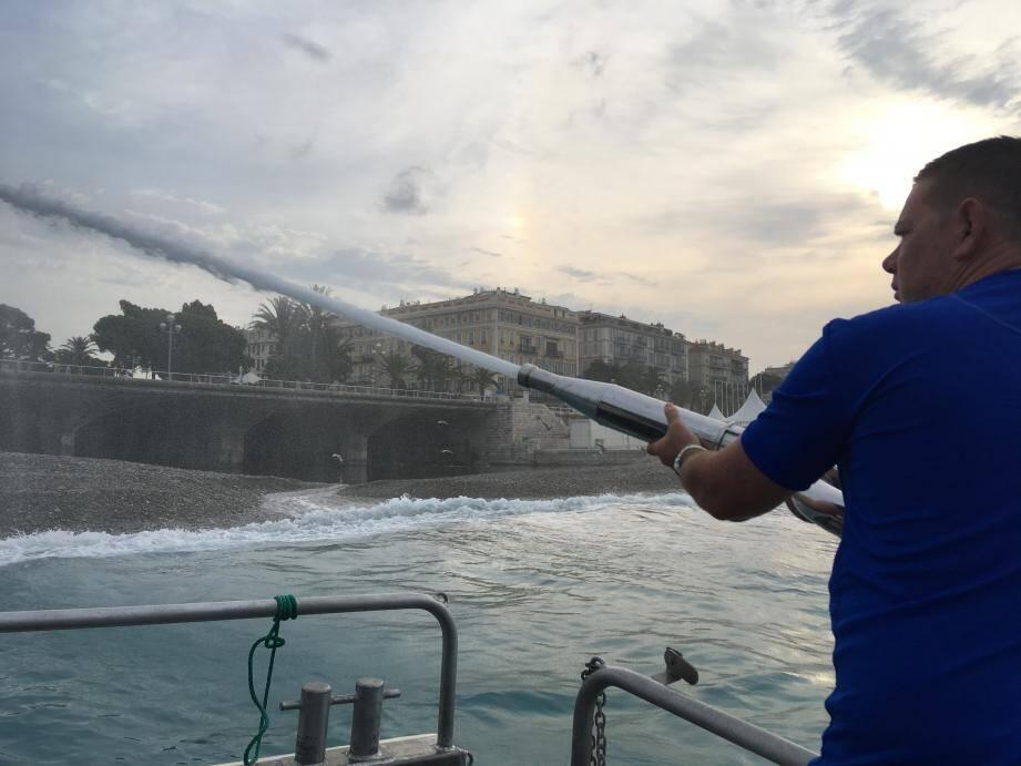 Fabien, membre de l'équipage du nettoyage du plan d'eau, utilise le canon pour laver les galets à distance.