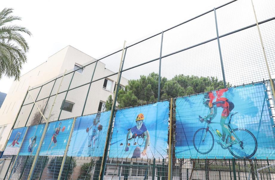 Les photos de sportifs pris sous l'eau exposées sur les grilles de l'ancienne école.