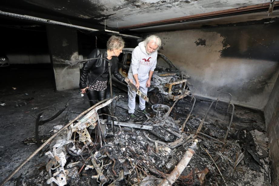 Christian et Florence, effondrés, devant les restes de leurs véhicules calcinés.