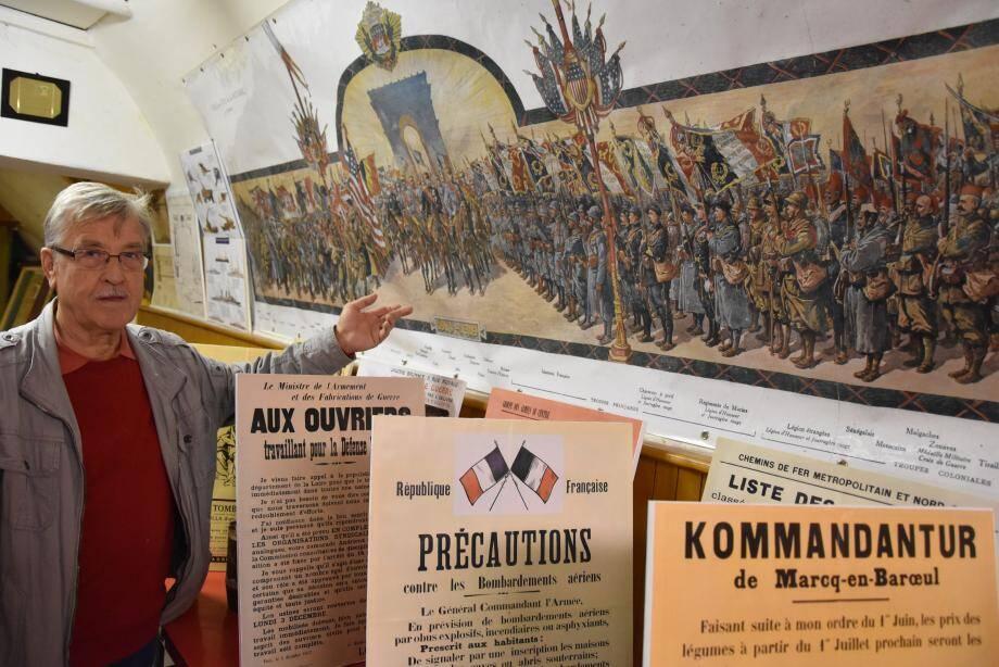 Achim Herget, président de l'APT, devant la fresque qui représente le défilé de la victoire avec, en bas, l'impressionnant inventaire des pays ayant participé au premier conflit mondial.