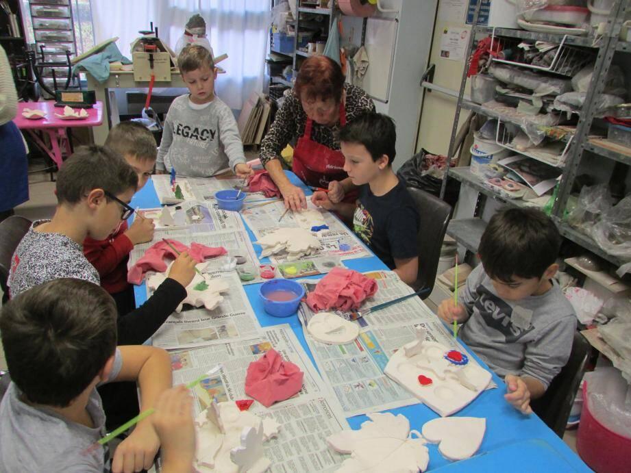 Suivant les conseils de leurs aînés, les enfants donner des couleurs à leur création.
