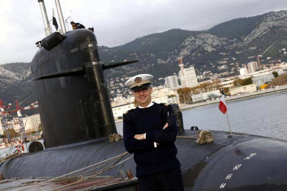 Le capitaine de vaisseau Cyril de Jaurias pose devant le SNA Saphir dans la darse de Missiessy.