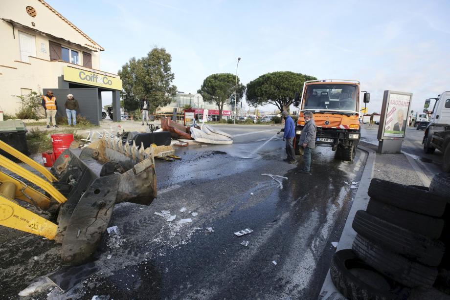 Les agents des services municipaux ont fort à faire pour nettoyer une chaussée dégradée par le barrage que les Gilets jaunes avaient mis en place cette nuit sur la route d'accès au dépôt pétrolier.