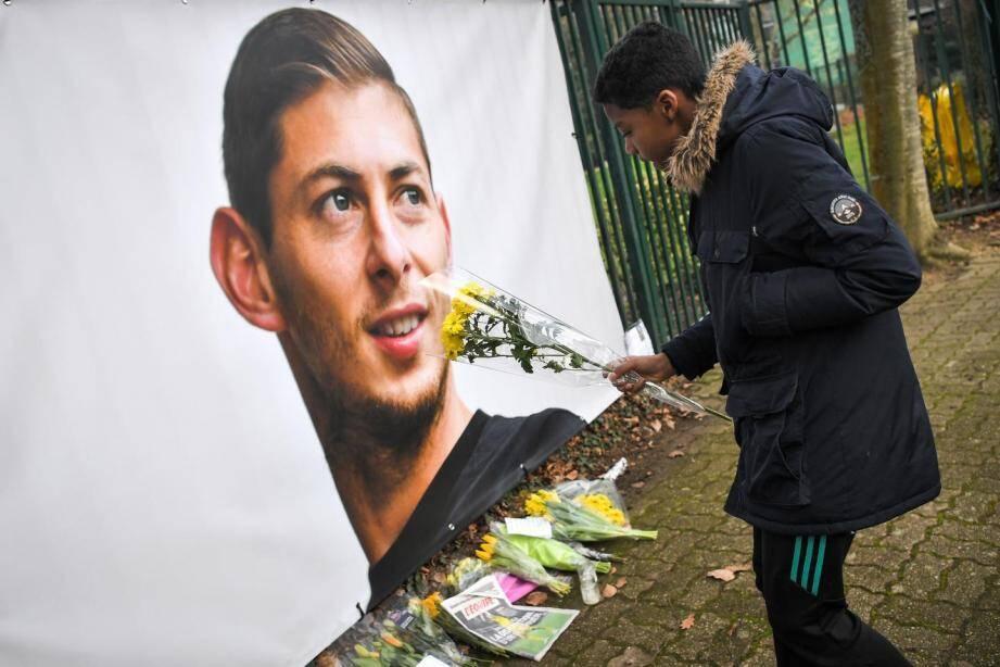 Un jeune homme pose des fleurs devant le portrait d'Emiliano Sala au centre d'entraînement du FC Nantes.