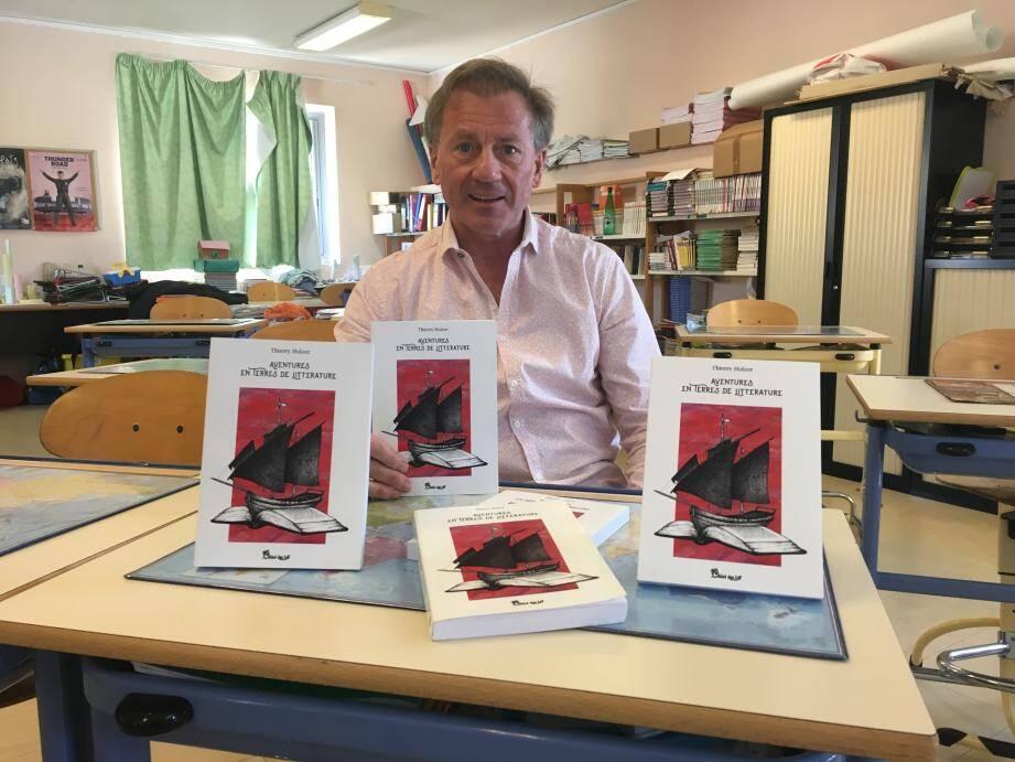 Thierry Holzer pose dans sa classe avec son livre « Aventures et terre de littératures ». Son prochain opus sera destiné aux enfants.