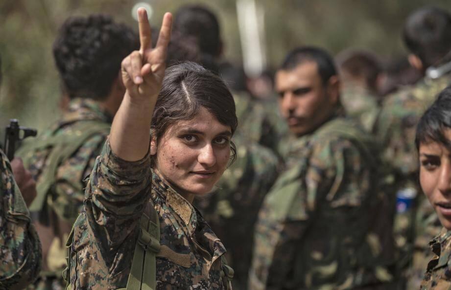 Une combattante kurde célèbre la victoire de la coalition à Baghouz sur le dernier bastion de l'Etat Islamique.