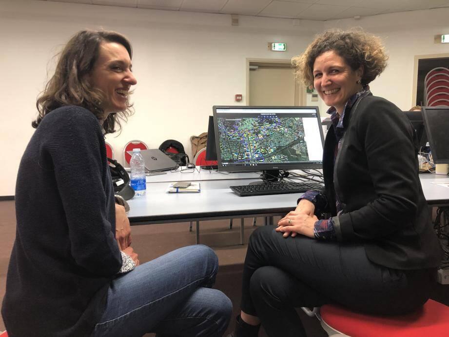 Mélanie Parent et Anabelle Maurel devant une carte thermographique représentant les déperditions énergétiques des habitations.