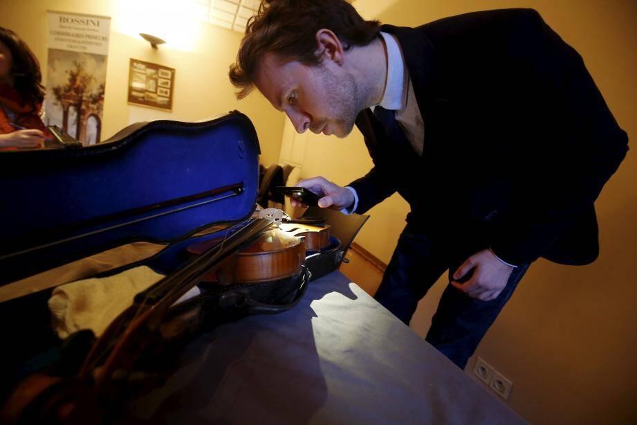 Le commissaire-priseur François-Xavier Poncet examine un violon et un archet qui datent du début du XIXe siècle.