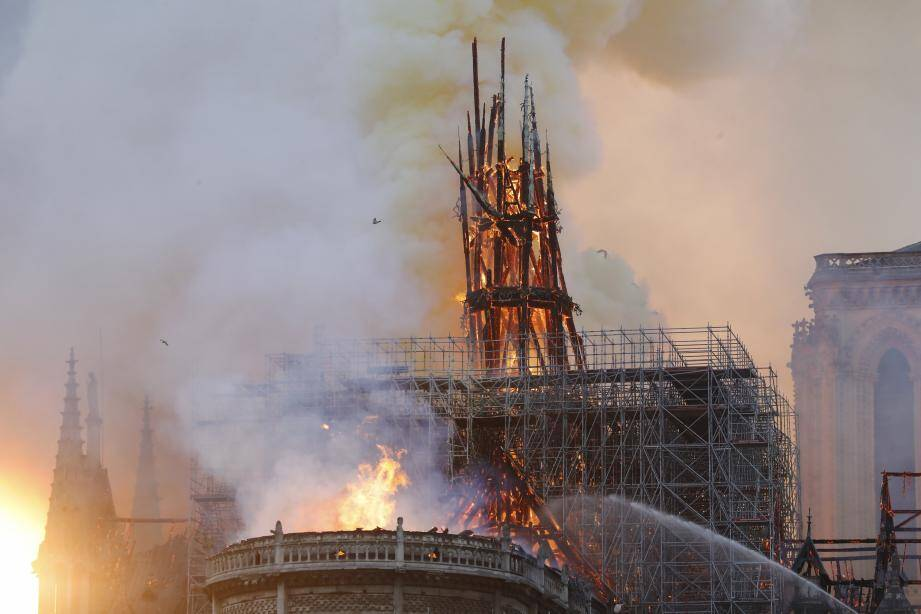 Smoke and flames rise during a fire at the landmark Notre-Dame Cathedral in central Paris on April 15, 2019, potentially involving renovation works being carried out at the site, the fire service said. - A major fire broke out at the landmark Notre-Dame Cathedral in central Paris sending flames and huge clouds of grey smoke billowing into the sky, the fire service said. The flames and smoke plumed from the spire and roof of the gothic cathedral, visited by millions of people a year, where renovations are currently underway. (Photo by FRANCOIS GUILLOT / AFP)