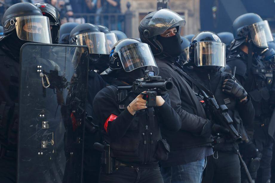 A police officer holding a non-lethal hand-held weapon (LBD40) fitted with a camera during an anti-government demonstration called by the