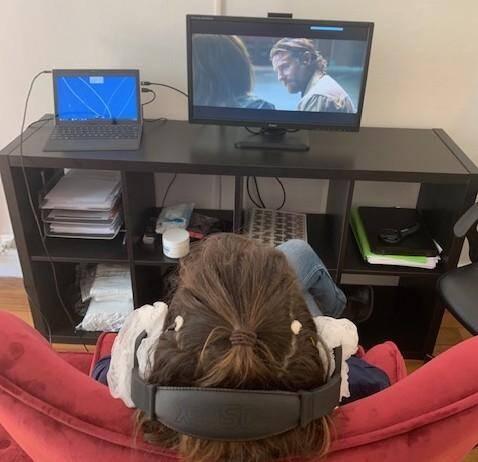 Un casque vissé sur les oreilles, concentré sur le visionnage du film, des signaux sur l'écran (barre bleue) signalent des changements brutaux d'activité cérébrale.
