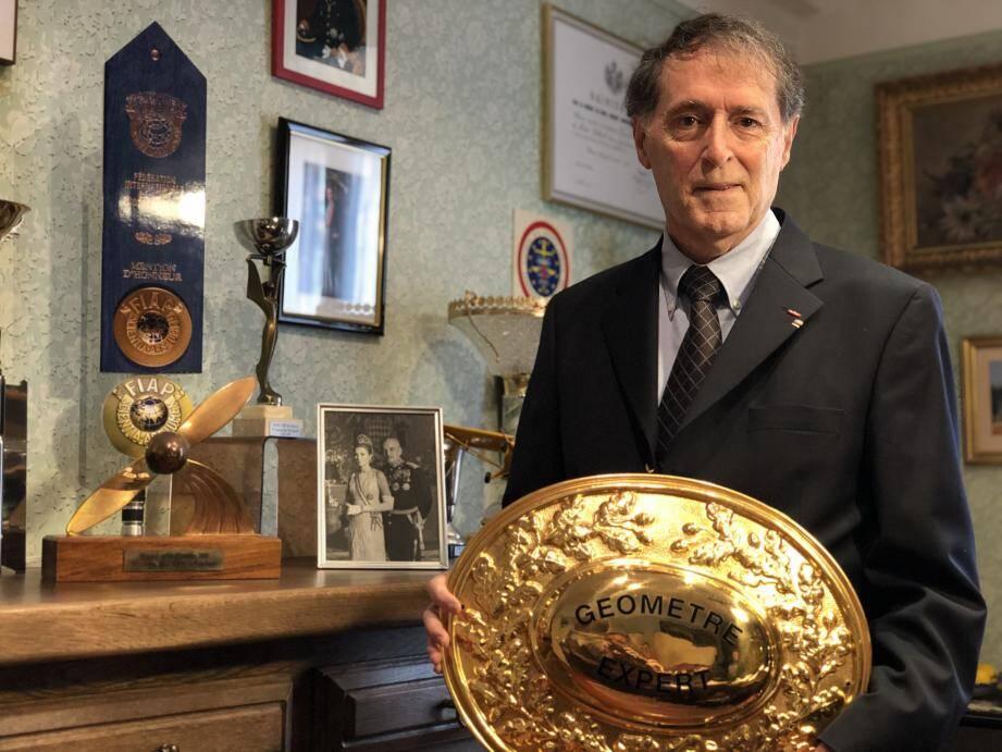 Jean-Bernard Rollin au milieu de ce qui compose son univers : l'Hélice d'or, la plaque dorée, des coupes et des photos...