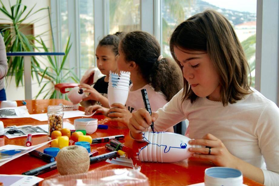 Les enfants réalisent, chacun à l'aide des mêmes matériaux, un requin-bilboquet.