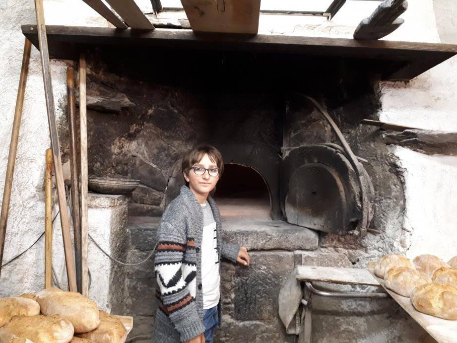 Ewan devant le four trois fois centenaire de la boulangerie « Chez Gégène » dans le village haut perché de Roure.
