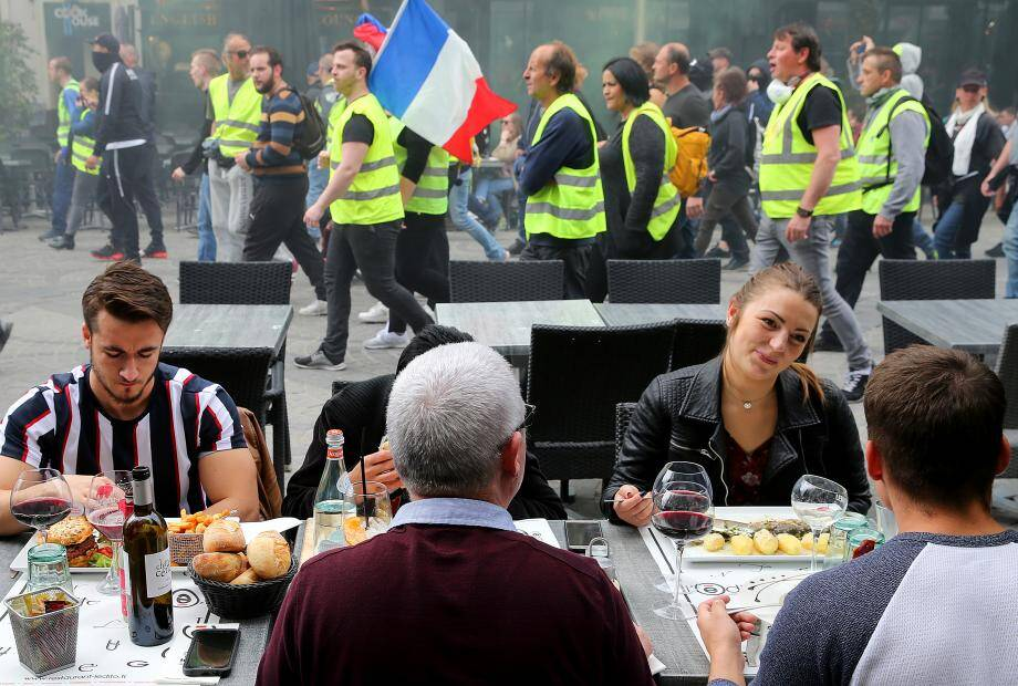 Protestors walk past a restaurant's terrace as people are having lunch during a demonstration called by the