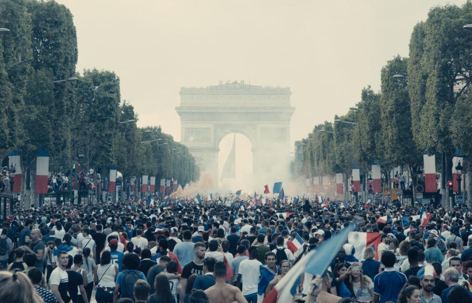 Un gamin sort d'un immeuble de Montfermeil avec un drapeau français enroulé autour du cou. Il rejoint un groupe de copains pour aller à Paris fêter la victoire de l'équipe de France de football...