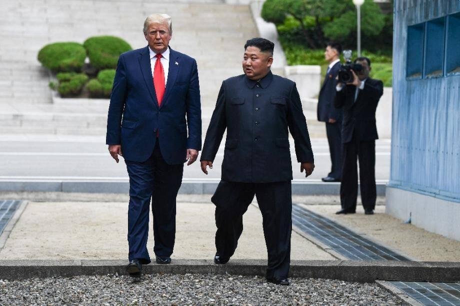 Le dirigeant nord-coréen Kim Jong Un et le président américain Donald Trump repassent dans la partie sud de la ligne de démarcation entre les deux Corées, après une brève incursion de Trump dans la partie nord, le 30 juin 2019.