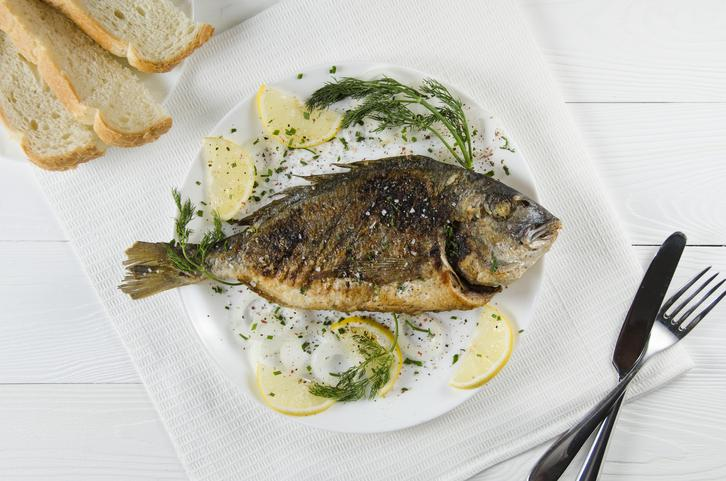 grilled dorado on a round white plate on a white wooden background on white napkin with a lemon dill and spices and cutlery