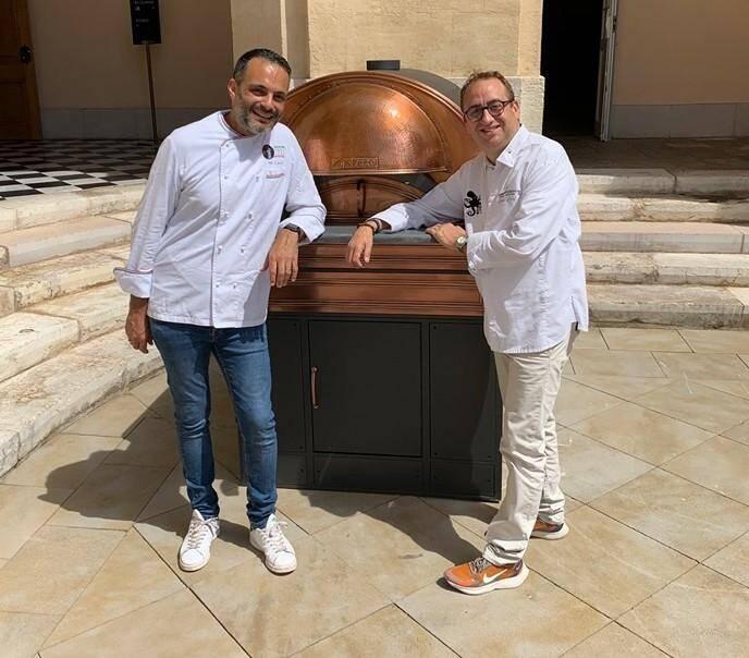 Le pizzaïolo Marco Casella et le chef étoilé Lionel Lévy devant le four à pizza importé de Naples pour donner corps à leur collaboration.