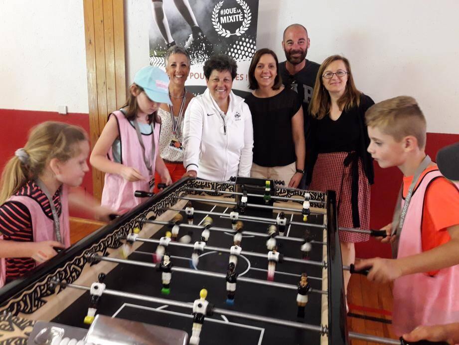 Devant les enfants découvrant le baby-foot mixte de l'ex-joueuse de foot Nicole Abar (en blanc), de gauche à droite: Sabine Bègue, Maud Bergeret, Cédric Allard et Cécilia Chevallier.