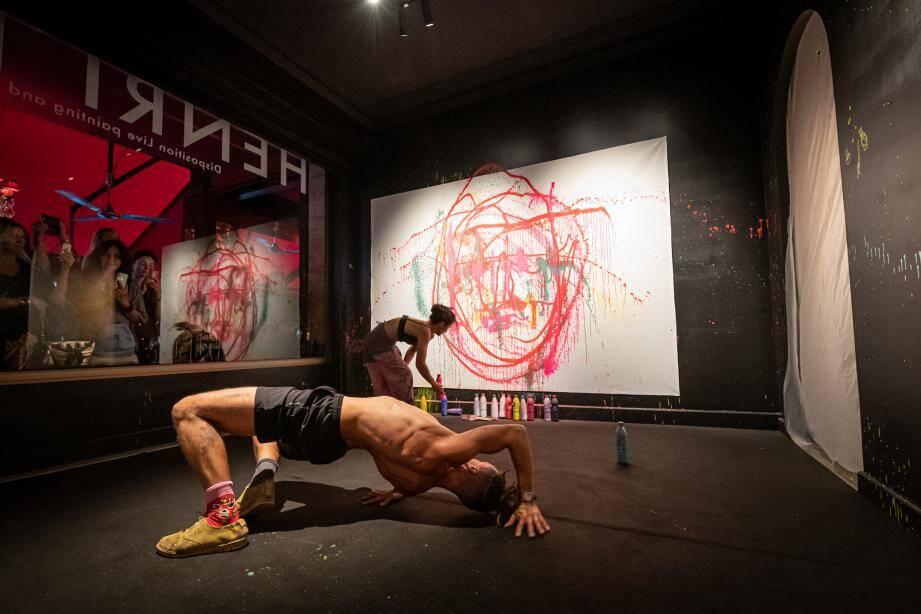 Peinture à la main, l'artiste enchaîne les mouvements de capoeira pour consteller une toile blanche de couleurs différentes.