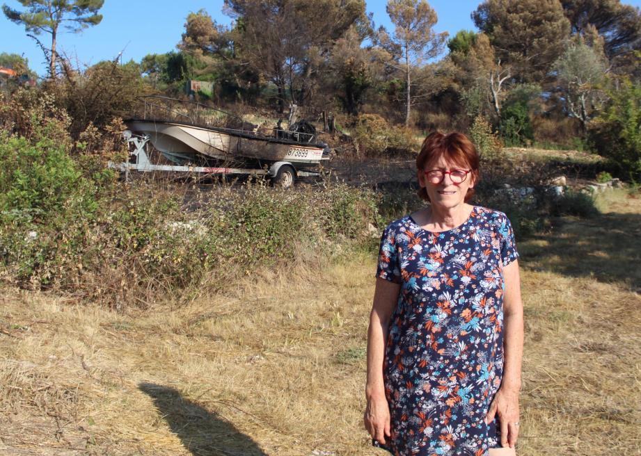 La propriétaire du chemin de Castellaras devant son bateau et la végétation brûlés.
