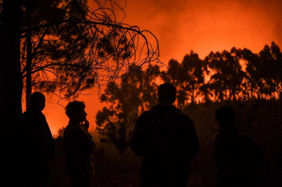 Des habitants regardent un incendie dans la forêt d'Améndoa, le 21 juillet 2019 au Portugal