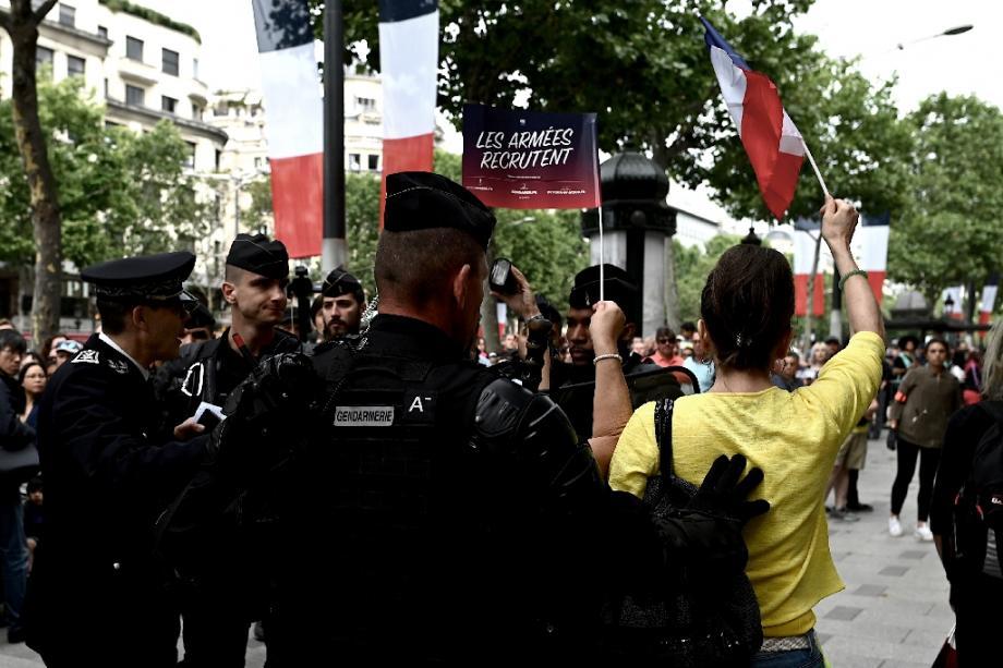 Des gendarmes entourent une femme qui a hué le passage du président de la République à Paris sur les Champs-Elysées le 14 juillet 2019