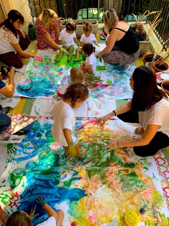 Enfants et enseignantes se servent de blocs de peinture glacée pour la création de deux tableaux.