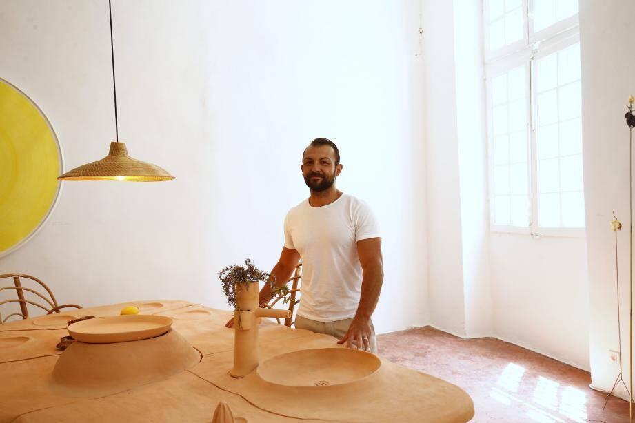 Carl Tran est un architecte d'intérieur toulonnais exerçant depuis plus de dix ans auprès de particuliers et d'entreprises. Il pose ici devant une table en terre cuite imaginée par François Champsaur.
