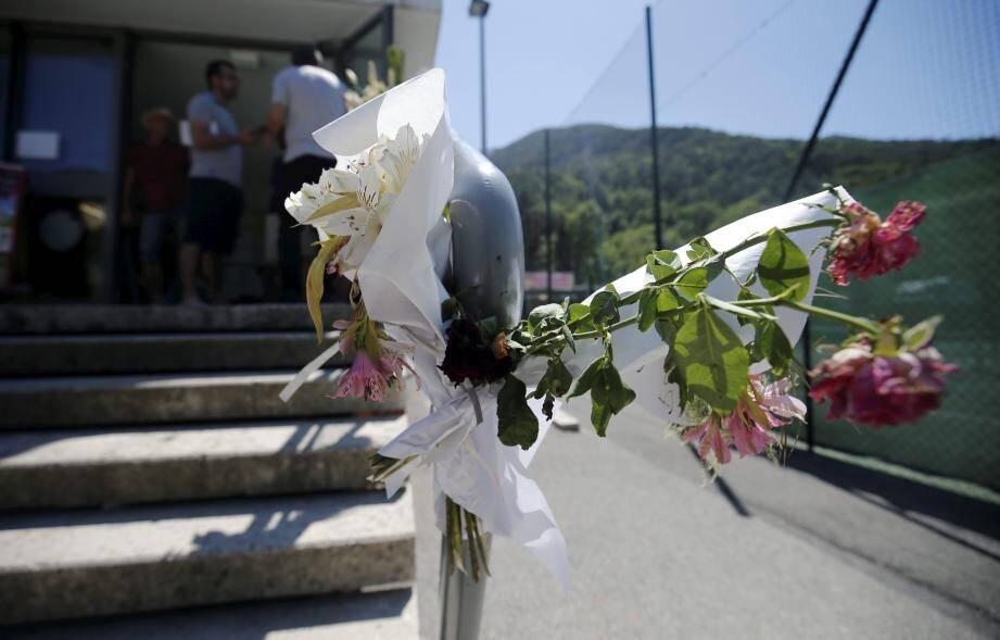 Des bouquets pleurent l'absence de celle qui a chuté en arrosant les fleurs en haut de l'escalier.