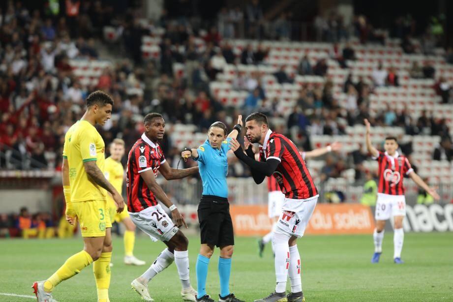 L'arbitre Stéphanie Frappart entourée par les joueurs de l'OGC Nice, lors d'un match contre Nantes.